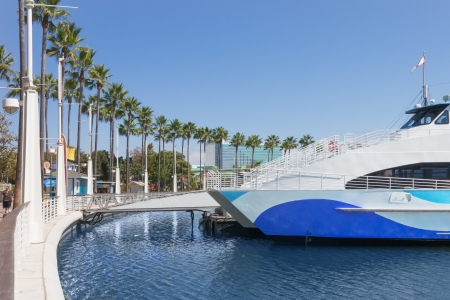 ship bow: Tour boat docked in Long Beach California city Tourist cruise ship bow, white metal railing to second story  Ramp walkway from dock  Blue sky  Palm trees line the curving marina  Tall building in background  Wide angle, perspective view  Horizontal photo