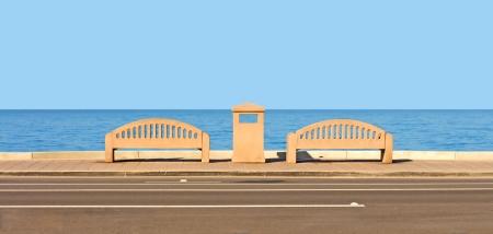botes de basura: Un par de bancos de piedra que mira sobre el océano lo alto, vista de la calle de las tranquilas aguas azules Back de bancos y piedra papelera Horizon y cielo despejado
