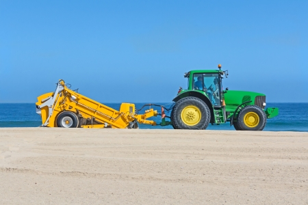 grader: Industrial heavy tractor and trailer grading sand on the beach   Side view of yellow and green machine sand grader  Clear blue water and sky, horizontal background