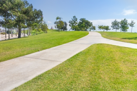 forked: Winding urban park path   Forked, paved pedestrian footpath changing direction  Trimmed grass  Trees in background  Blue sky, some clouds  Horizontal landscape scene  Stock Photo