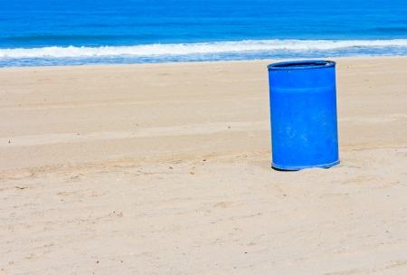 uncluttered: Blue metal trash can on uncluttered sand   Clean beach on a sunny day  Waves, blue ocean and sky background  Horizontal photo