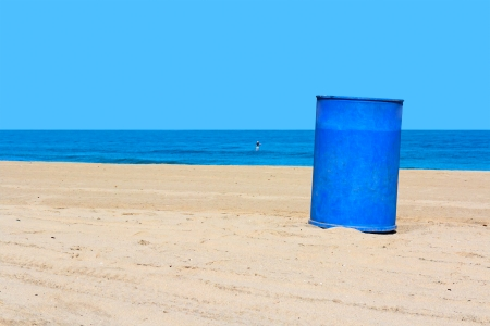 uncluttered: A clean beach on a sunny day   Blue metal trash can on uncluttered sand  Person in water, Blue ocean and sky background  Horizontal photo