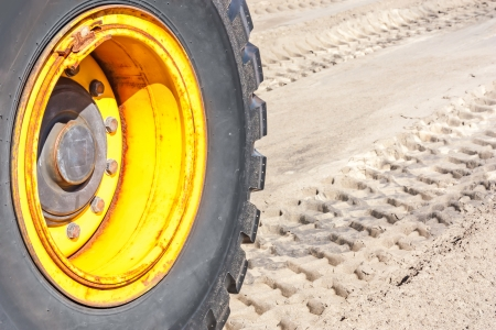 Row of deep tractor tire prints in the sand   Close up of industrial vehicle heavy black rubber tire, bright yellow metal wheel  Horizontal photo  photo