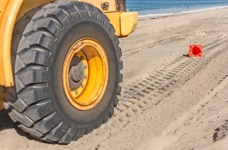Large tractor tire leaves tread tracks in the sand on the beach   Close up of industrial vehicle heavy black tire  Fallen orange traffic cone, ocean, waves in background  photo