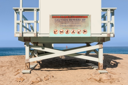 underneath: View from under the lifeguard tower   Looking at the sand, blue ocean and sky from behind and underneath the hut  Sign warning to swim near a lifeguard  Person paddle boarding in the background  Horizontal scenic photo