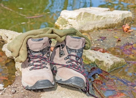 Socks on top of shoes resting on rock  Wet leaves in the murky water  Nice for a relaxing, wilderness concept  Horizontal landscape photo