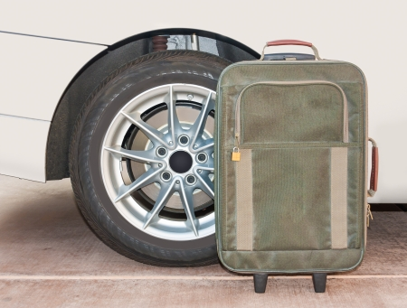 Green khaki bag, zippered front pocket with small padlock  Rear side of white car, tire and wheel in background  Cement surface   photo