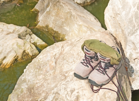 murky: Socks on top of shoes resting on rock  Green, murky water  Nice for a relaxing, wilderness concept  Horizontal landscape photo  Stock Photo