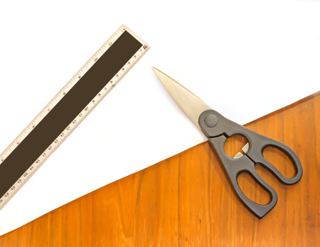 Closed scissors, 12 inch plastic ruler on blank sheet of white paper    Textured wood background  photo