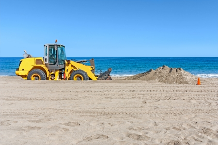 construction machinery: Beach backhoe with pile of sand   Heavy construction equipment vehicle digging sand by the ocean  Orange traffic cone  Clear blue sky, calm water in background