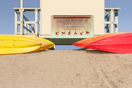 Group of kayaks stacked together on sand behind lifeguard tower   Vivid colors, yellow and red  Rear view from under hut  Clear blue sky  No water or ocean in photo  Horizontal scene   photo