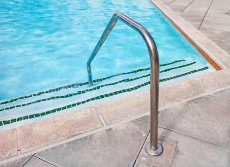 pool bar: Swimming pool handrail at shallow end   Steel grab bar for safety  Steps leading into clear blue rippling water  Grey stone tile  Horizontal photo