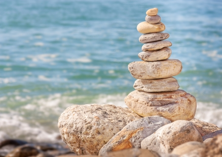 meditation stones: Zen stones with ocean wave background   Neatly ordered pyramid shape rock pile balanced on larger rocks