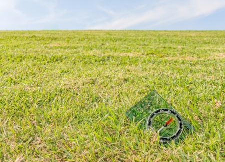 Plastic compass on green grass field   Blue sky, wispy cloud background  Horizontal nature scene  photo
