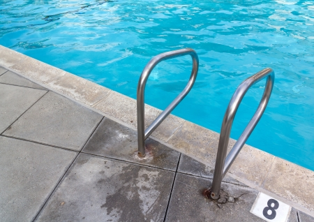 pool bars: Swimming pool handrail at deep end    Steel grab bars for safety at 8 feet water depth  Grey stone tile  Clear blue rippling water  Horizontal photo  Stock Photo