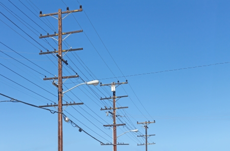 Trio of telephone utility poles, cables, streetlights, and clear blue sky background   Neat rows of parallel distribution wires connected to three tall wood posts  Perspective view  photo