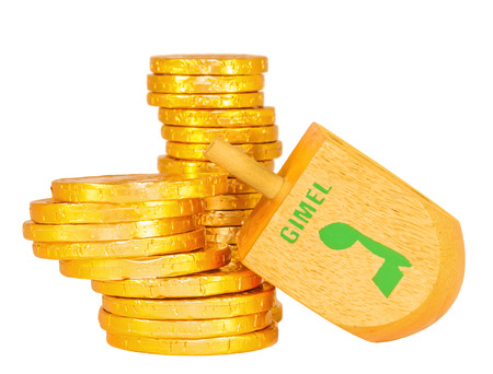 Stacks of Chanukah coins and large wooden dreidel   Dreidel is a traditional game for the Jewish holiday of Chanukah   The Hebrew letter gimel wins the group of shiny wrapped chocolate coins  photo