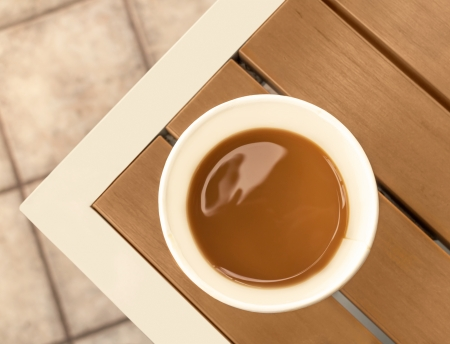 table top: Coffee with milk in disposable paper cup on wood table   View from above  Wooden slat table with metal frame  Tile floor, blurred background  Horizontal photo