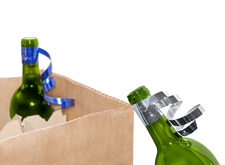 boxed: Empty glass wine bottle with ribbon leaning against cardboard shipping box   Uncorked bottle, green glass  Full corked bottle inside box  Curly silver and blue ribbons  Blurred, isolated white background  Horizontal photo   Stock Photo