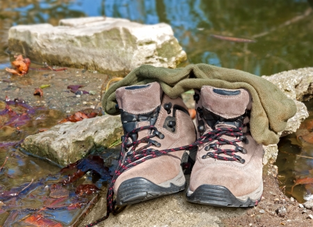 murky: Unlaced brown hiking boots and green socks by the pond   Socks on top of shoes resting on rock  Wet leaves in the murky water  Nice for a relaxing, wilderness concept  Horizontal landscape photo