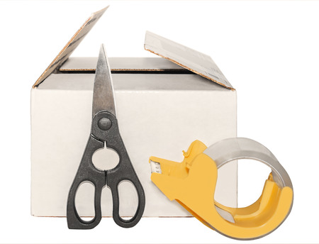 White cardboard box, scissors, yellow plastic tape dispenser  Package shipping tools  Heavy duty shears, roll of clear tape in front of partly open shipping container with closed and open flaps  Concept of box just opened, sealed, or resealed     photo