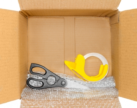 sealing tape: Packing tools inside corrugated box    Open brown cardboard box, scissors, bubble wrap, yellow plastic clear tape dispenser roll  Isolated on a white background  Horizontal photo