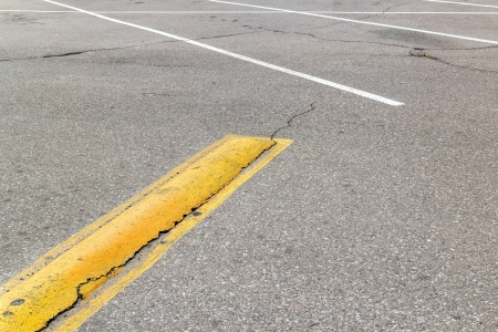 Parking lot concrete yellow speed bump   A symbol of warning vehicles to drive slowly for safety  Cracks in grey asphalt surface  Horizontal photo  photo