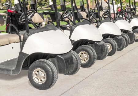 Row of white golf carts parked on pavement  Close up, front view     Line of electric buggies showing tires, steering wheel, padded seats  Water bottle attached to vehicle  Person, trees in background  Horizontal photo  photo