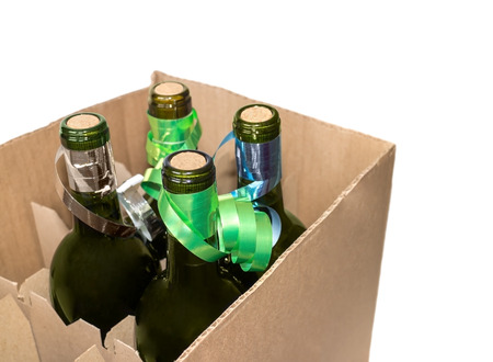 Four glass wine bottles decorated with ribbons in cardboard box   Corrugated shipping container with dividers  Isolated on a white background  photo