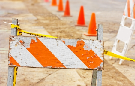 impede: Old wood and metal construction barricade on broken pavement and dirt   Orange and white sign with yellow ribbon  Line of orange plastic traffic cones in blurred background  Horizontal scene  Stock Photo