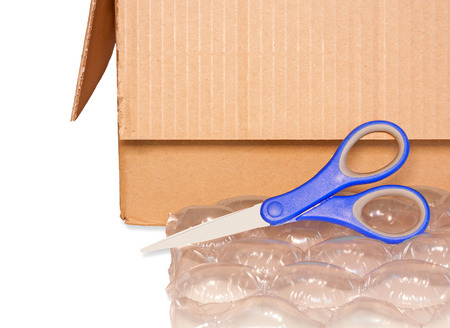 the padding: Box, scissors, and bubblewrap   Brown cardboard container, open flaps  Large puffy bubbles for package padding and protection  Shears with blue plastic handle  Horizontal, isolated on a white background  Stock Photo