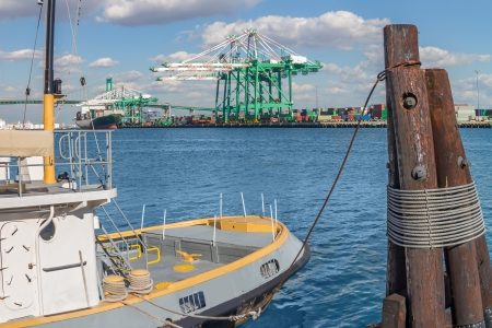 Small boat tied to wood post at Port of Los Angeles   Gantry cranes, container ship, freight containers, shipping terminal, Vincent Thomas bridge in background  Blue sky with clouds  Horizontal harbor scene