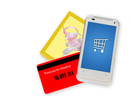 Buying online with a cell phone  Fast, easy internet shopping made with a credit card phone app   Smartphone with shopping cart icon on screen, back of red credit card, yellow gift box with ribbon  Horizontal, isolated on a white background  photo