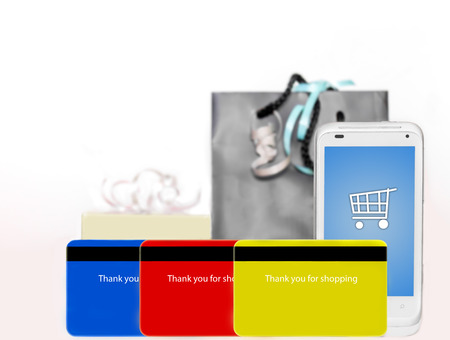 Buying online with a cellphone  Fast, easy internet shopping made with a credit card phone app   Smartphone with shopping cart icon on touch screen, 3 credit cards, gift box and bag with ribbons  Horizontal, isolated on a white background  photo