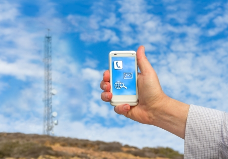 Male hand holding a cell phone in the air   Communication tower and blue sky with clouds background. photo