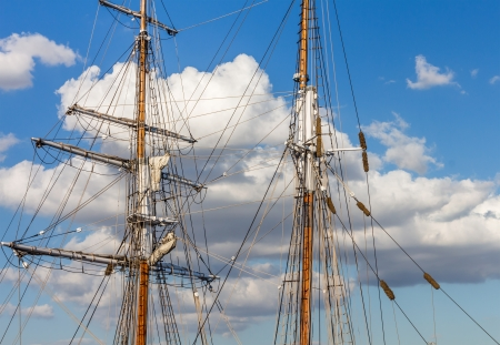 rigging: Old ship mast and rigging   Antique style sailing vessel. Blue sky with cloud background  Stock Photo