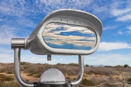 far away look: Front of outdoor daytime viewing telescope in rural area. View of blue sky and clouds reflection in glass.
