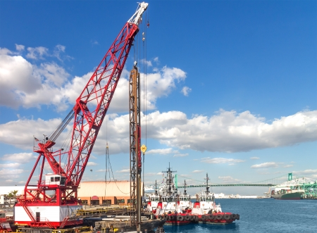 Construction site, port of Los angeles   Heavy industrial hook and pulley crane working at harbor renovation  Boats, Vincent Thomas bridge in background  Blue sky with clouds  Horizontal scene  photo