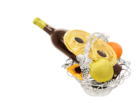 Elegant Jewish Purim holiday silver fresh fruit basket, wine bottle, party mask, hamantashen, apple, orange  Horizontal, isolated on a white background  Stock Photo