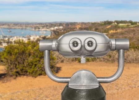 far away look: Outdoor daytime viewing telescope on hilltop overlooking a harbor   Back of tilt, swivel binocular scope  Two round eyepieces  Harbor, hillside in blurred background  Horizontal scene