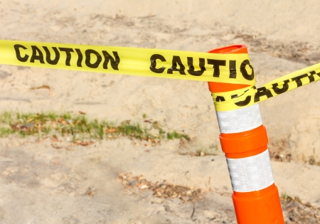 impede: Construction site sign   Bright yellow caution ribbon tied to plastic orange post with reflective white tape  Sandy