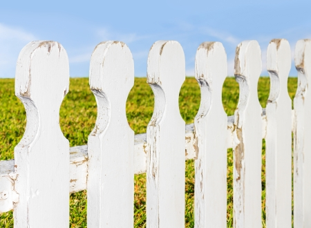 other side of: Popular saying, grass is greener on the other side of the fence   White wood picket fence, old with chipped paint, perspective view  Green grass, wispy clouds, blue sky blurred background  Horizontal landscape photo  Stock Photo