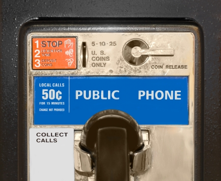 Old public pay phone, close up   Detail of coin operated telephone with coin slot and release handle  Black receiver in cradle  Instructions on how to make a call  photo