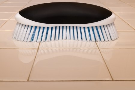tile grout: Scrub brush and clean tile countertop   Blue and white plastic bristles, black handle  Reflection in ceramic tile shiny surface  Profile view, horizontal photo  Stock Photo