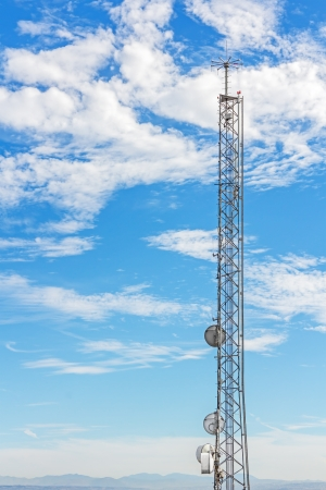 Sky high cell phone tower   Tall telecommunications steel structure  Mountains, blue sky and clouds background  Vertical view   photo