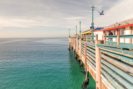 Strolling along the old wood pier, Redondo Beach, California   Calm water front  Blue sky and clouds, horizon background  Painted structure, chipped paint  Row of tall lamps  Perspective view