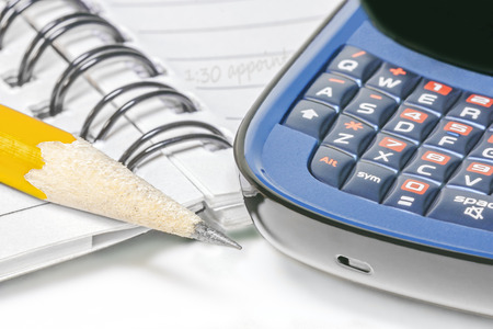 reminder concept: Business appointment reminder concept using paper and pencil or smart phone   Ring notebook, yellow wood pencil, cell phone keypad close up