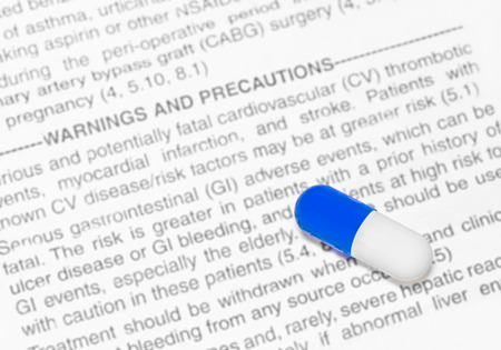 adverse reaction: Prescription drug warning and side effects concept   Blue and white pill capsule on blurred text