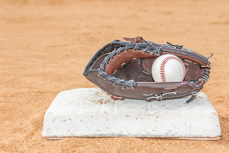 Baseball mitt and ball touching base in red sandy dirt infield   Ball inside glove  Low angle view, blurred room for text, copyspace  Horizontal photo   photo