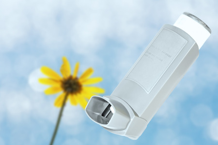 Asthma allergy inhaler sprayer with blurred blue sky, backlit yellow flower, bokeh Open, plastic inhaler  One wildflower on long thin stem  Breathing fresh air in nature concept  Horizontal photo   photo
